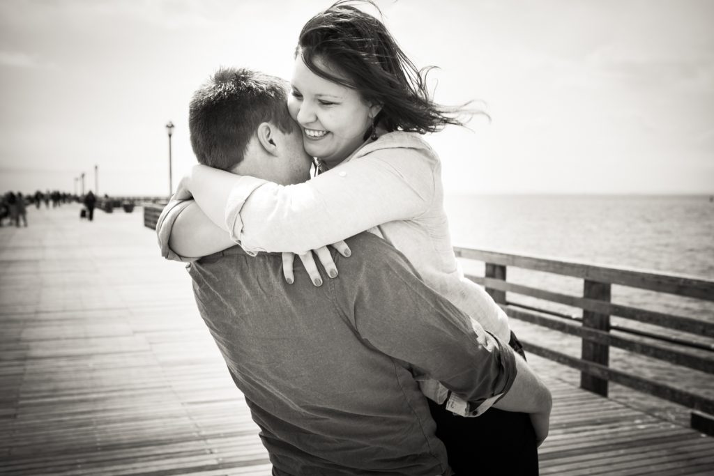 Black and white photo of man lifting up woman on Coney Island boardwalk