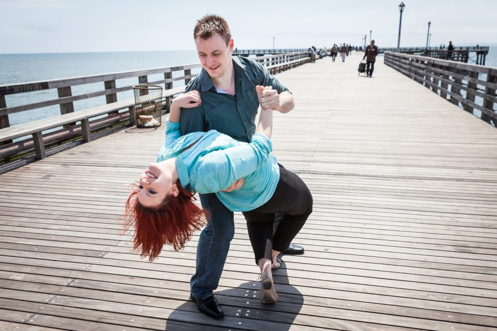 Coney Island engagement photos of couple dancing on boardwalk