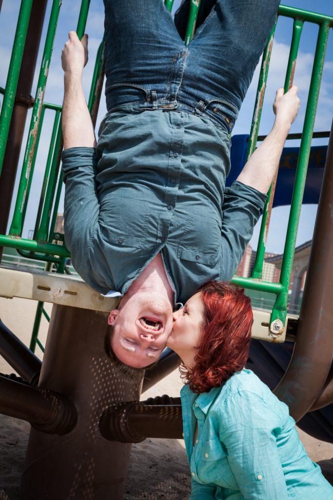 Man upside down on jungle jim kissing woman