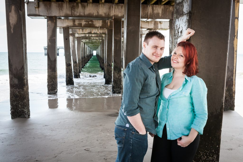 Coney Island engagement photos of couple leaning against column under pier