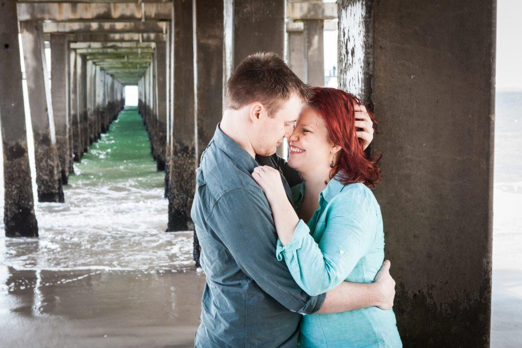 Couple hugging against column under Coney Island pier