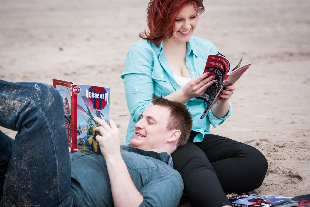 Coney Island engagement photos of couple reading comic books on beach