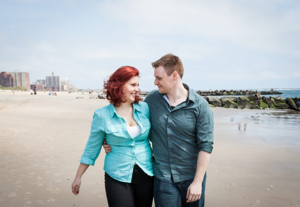 Coney Island engagement photos of couple walking on beach