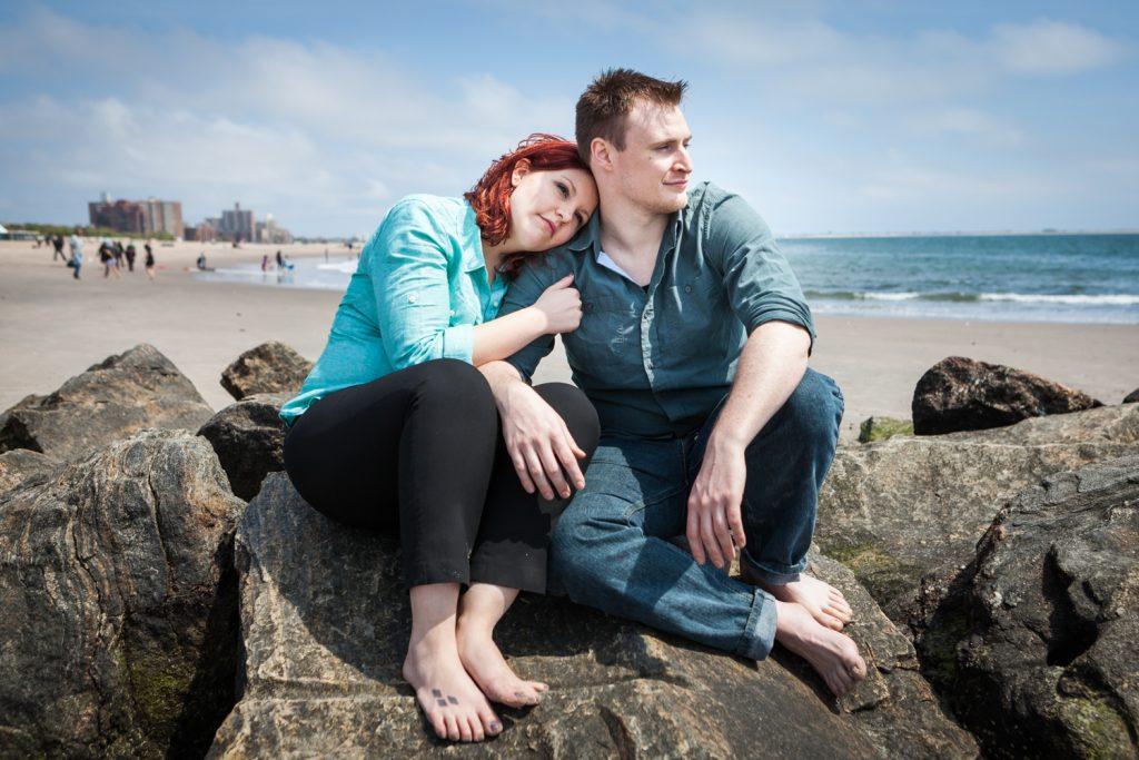 Coney Island engagement photos of couple sitting on rock