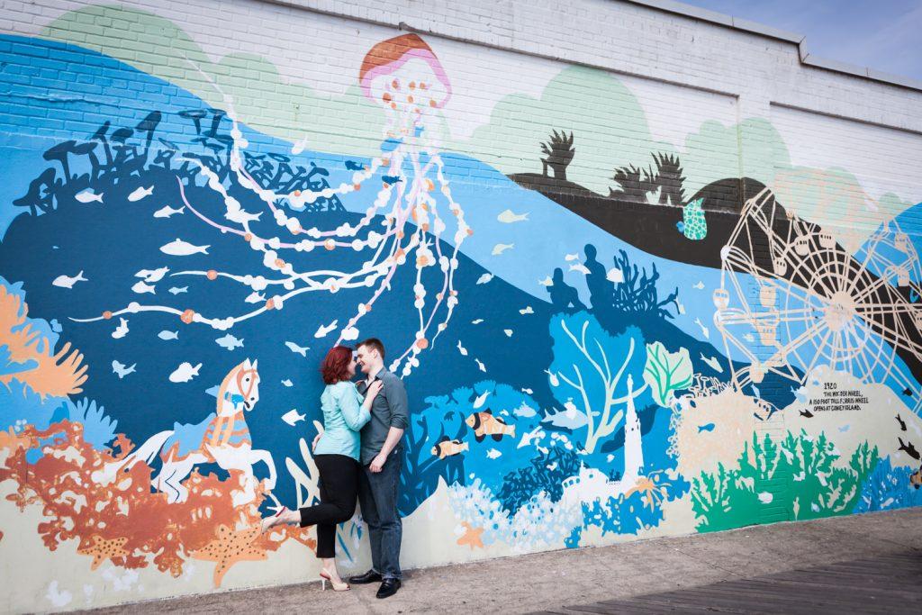 Couple hugging against colorful New York Aquarium mural