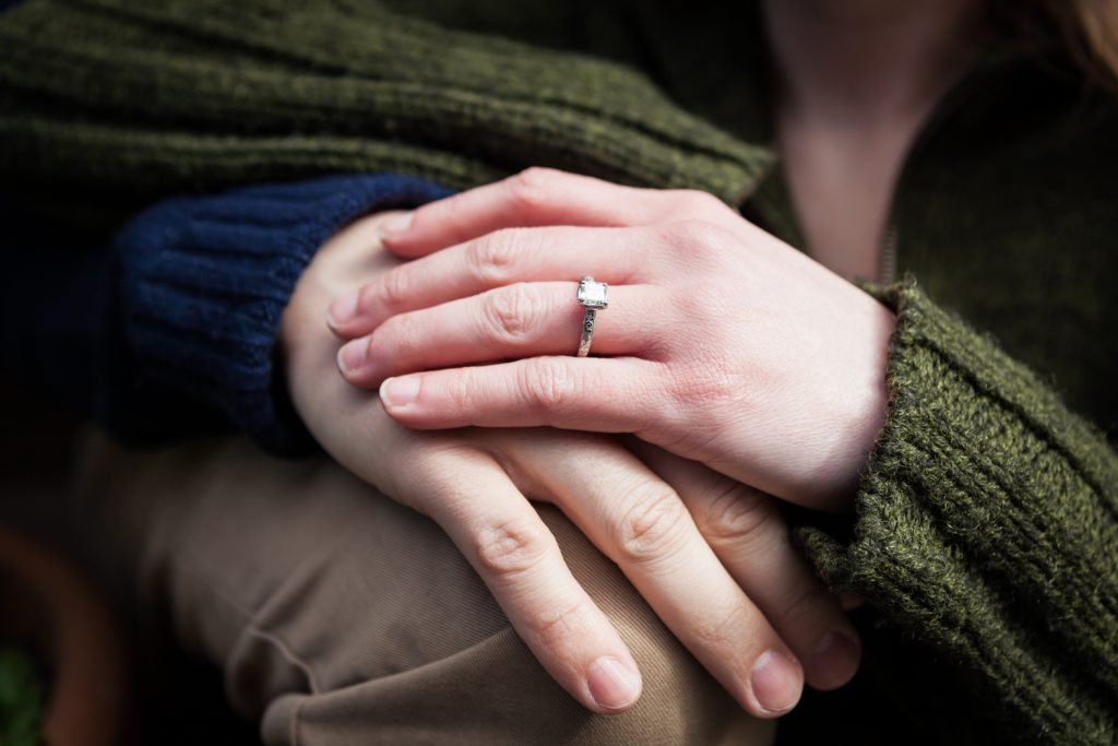 Close up on couple's hands with woman wearing engagement ring