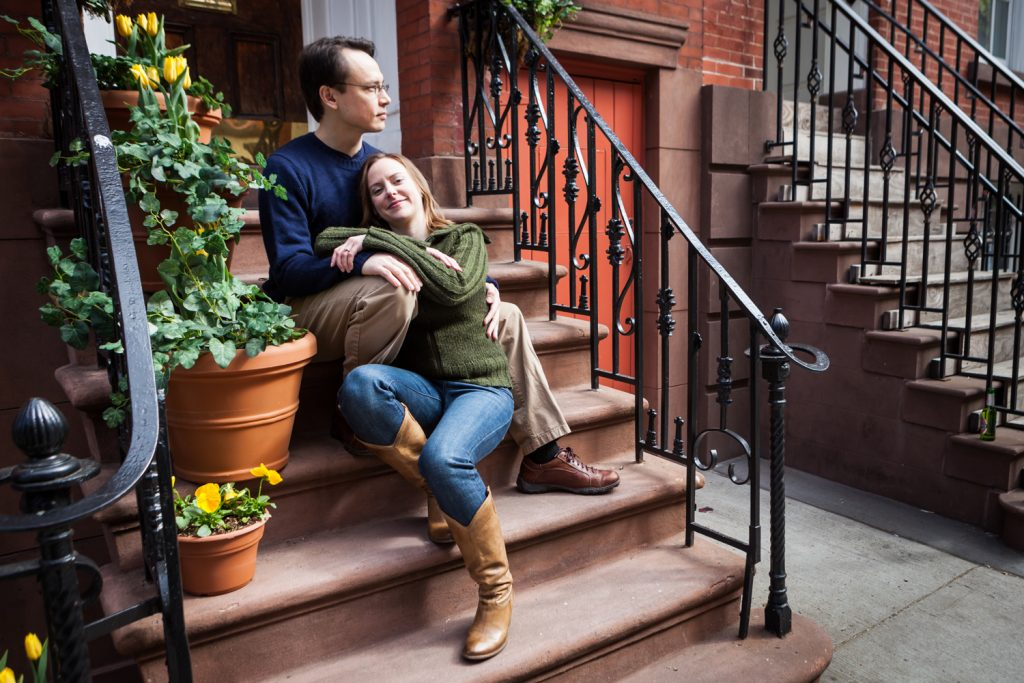 Couple cuddling on brownstone stairs in Greenwich Village