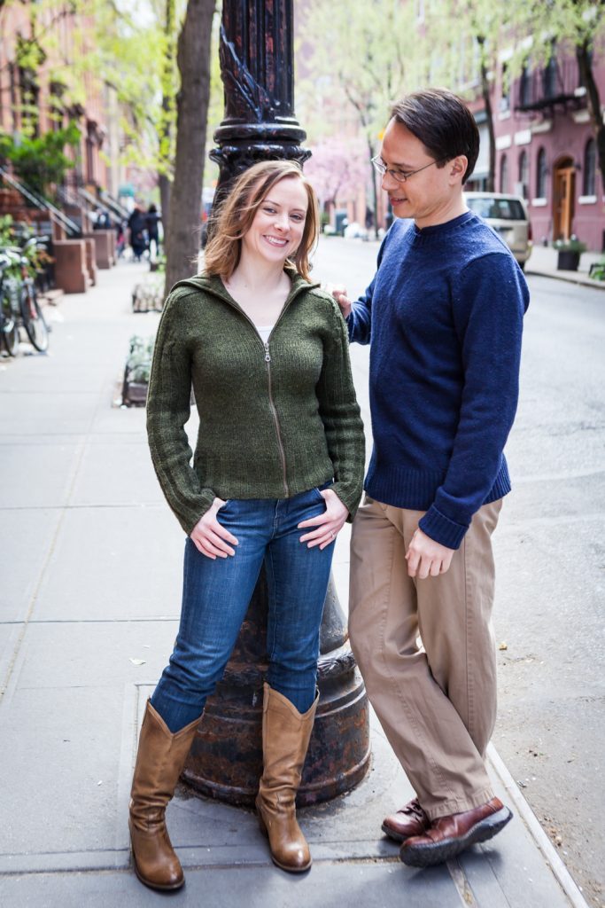 Couple leaning against light post in Greenwich Village