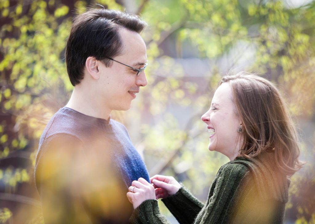 View through leaves of couple laughing during High Line engagement portrait session