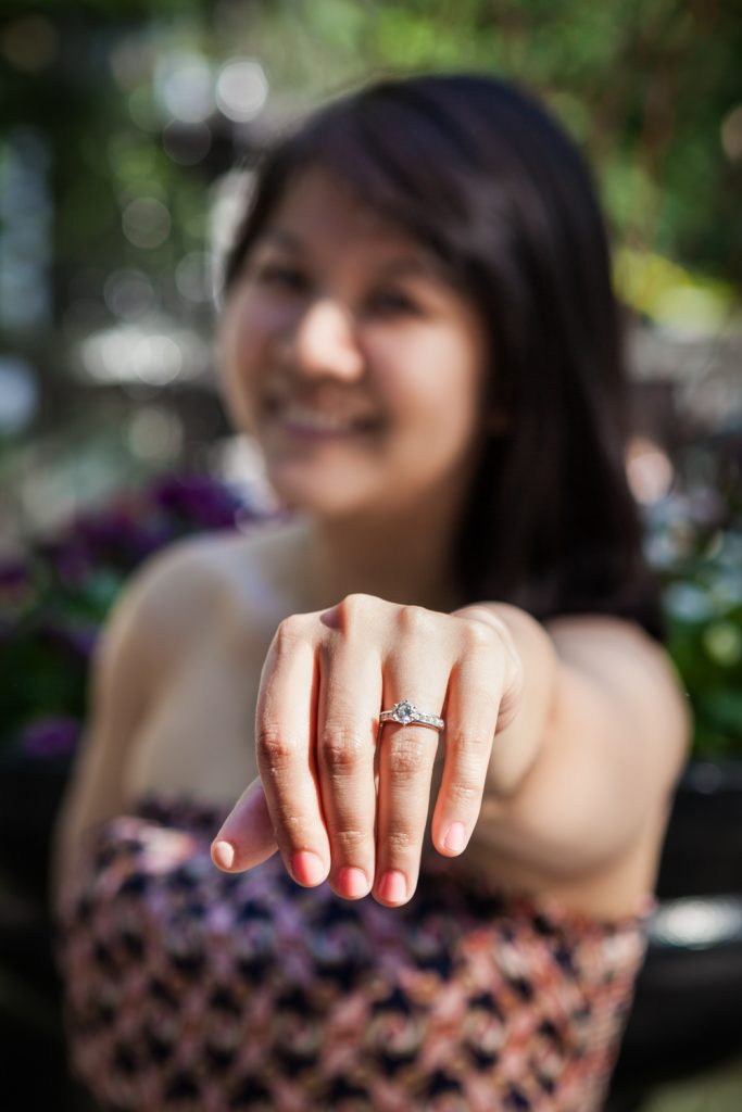 Woman holding hand out wearing engagement ring