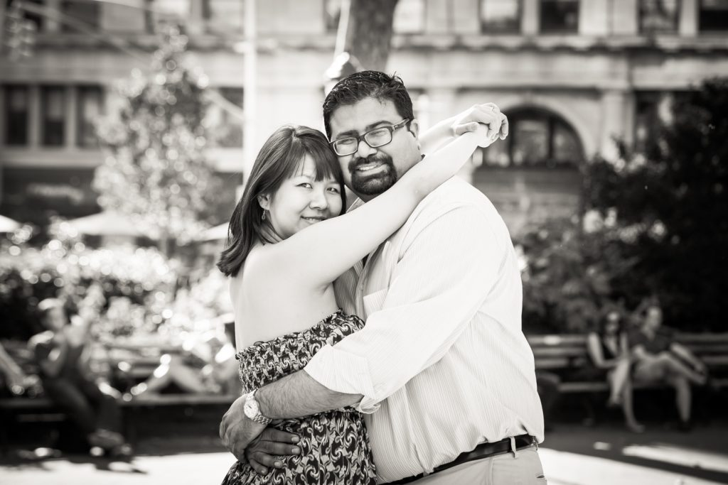 Black and white photo of couple hugging in Madison Square Park