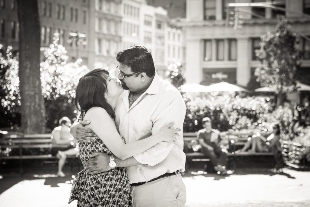 Black and white photo of couple kissing in Madison Square Park