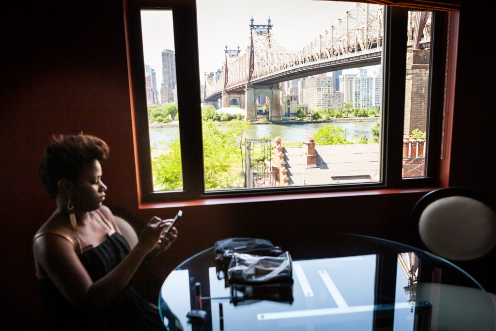 Guest sitting in front of window with Queensborough Bridge in background
