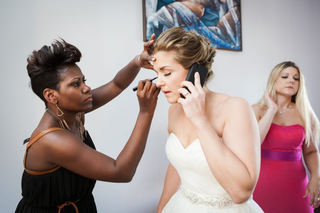 Bride getting makeup done while talking on cell phone
