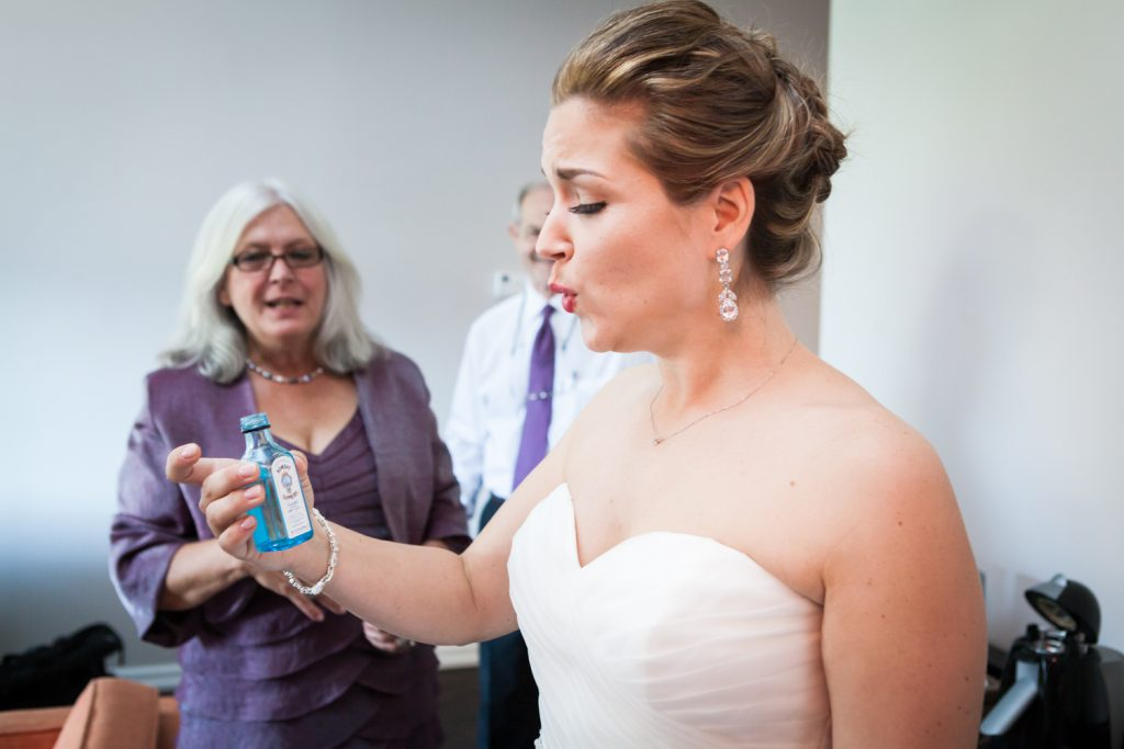 Bride taking a drink of gin from a small bottle before a Ravel Hotel Penthouse wedding