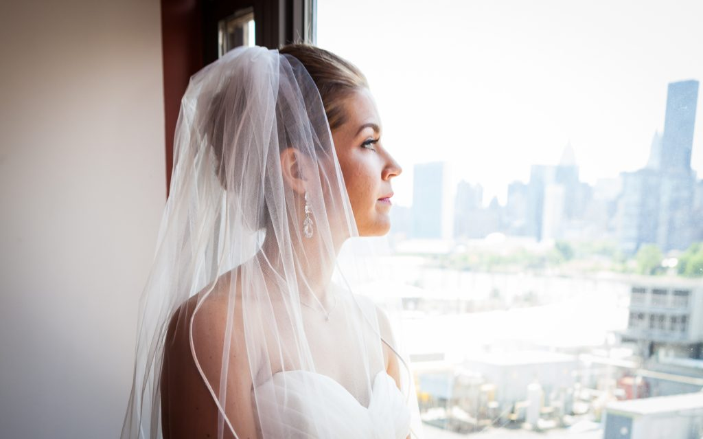 Portrait of a bride looking out window before her a Ravel Hotel Penthouse wedding