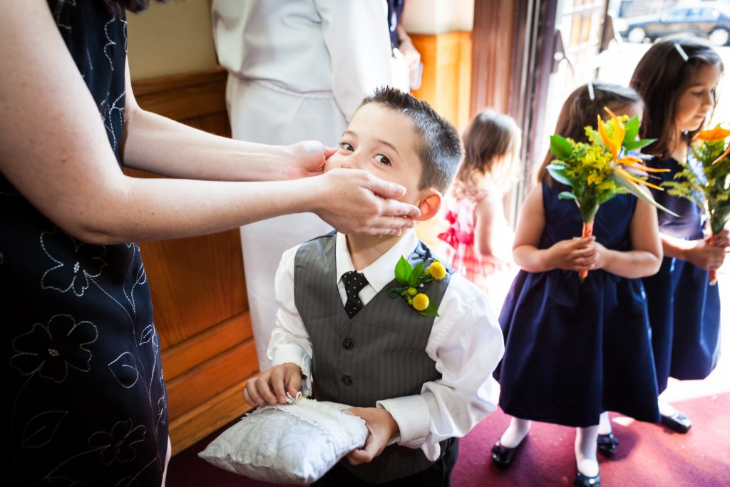Close up of woman holding little ring bearer's face