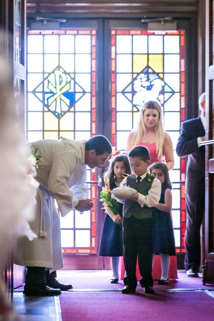 Priest giving instruction to little ring bearer