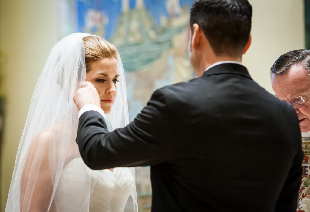 Groom brushing tear from bride's cheek in a Ravel Hotel Penthouse wedding