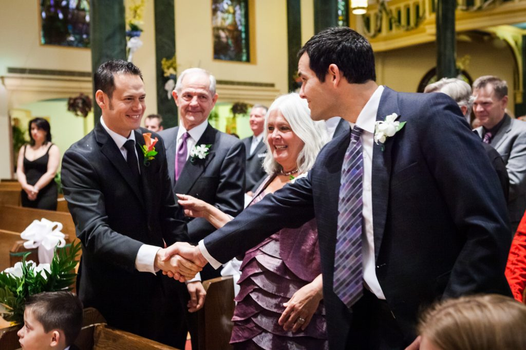 Groom shaking hands with family members in St. Joseph's Church