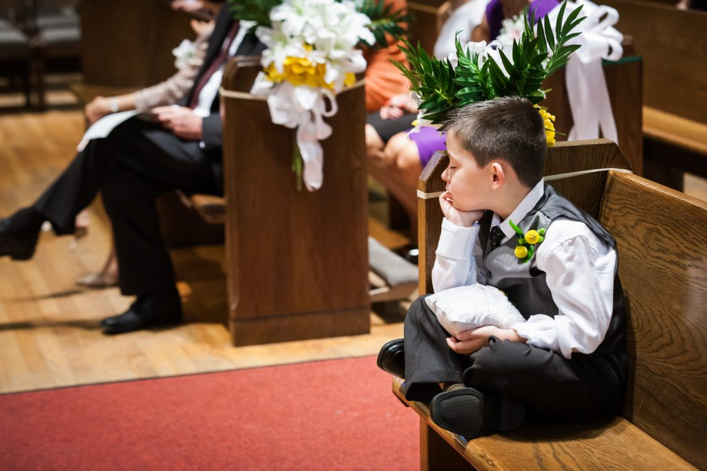 Little ring bearer asleep in pew during wedding ceremony