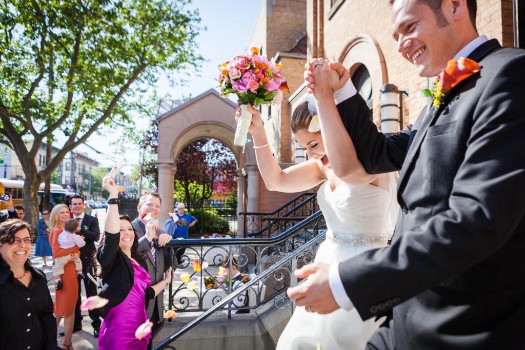 Bride and groom leaving St. Joseph's Church and guests throwing rose petals