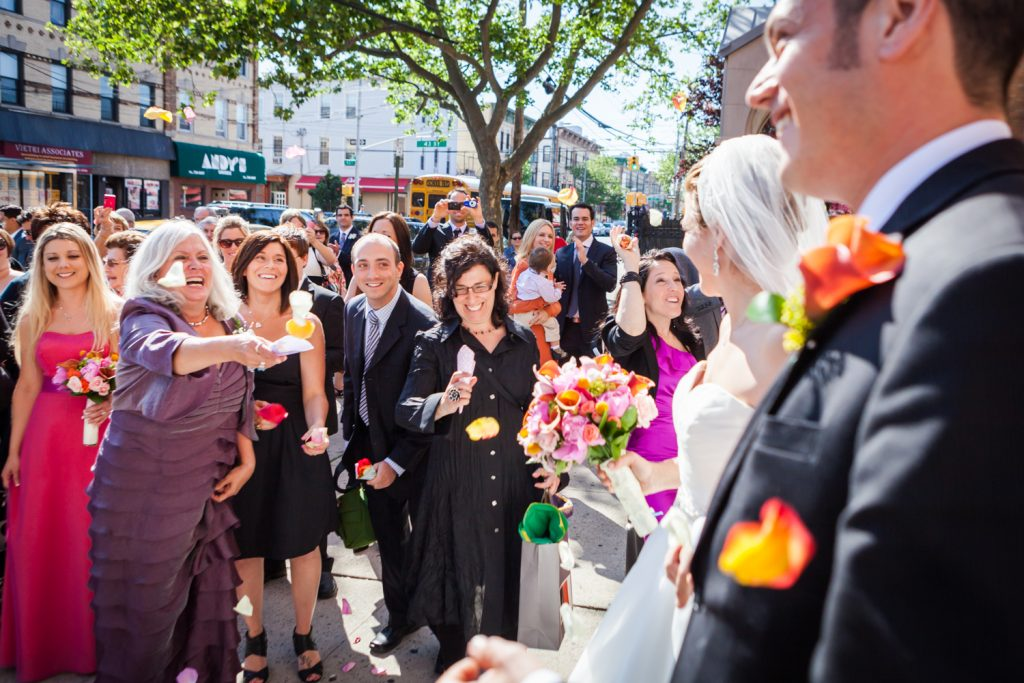 Guests throwing rose petals at bride and groom after wedding ceremony