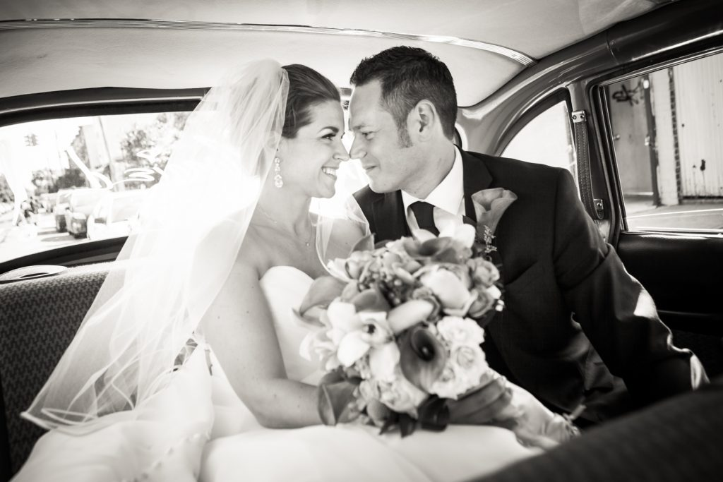 Bride and groom in back of taxicab after a Ravel Hotel Penthouse wedding