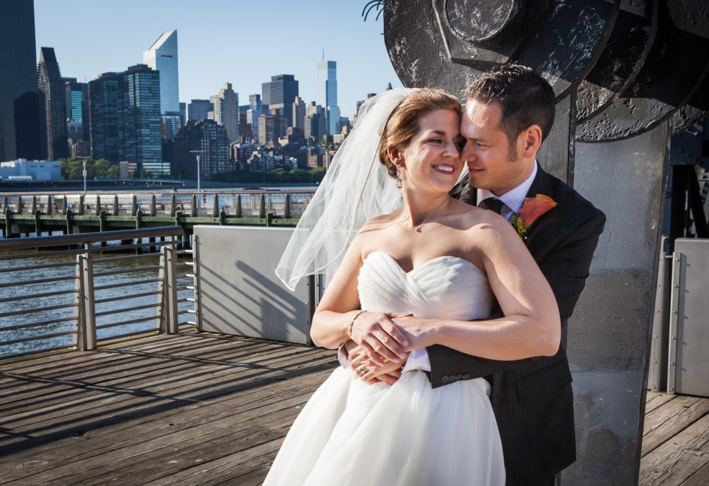 Bride and groom hugging in Gantry Plaza State Park during a Ravel Hotel Penthouse wedding