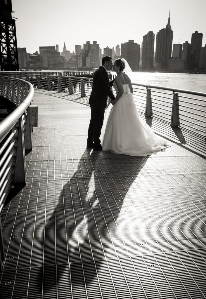 Bride and groom kissing with long shadow in Gantry Plaza State Park