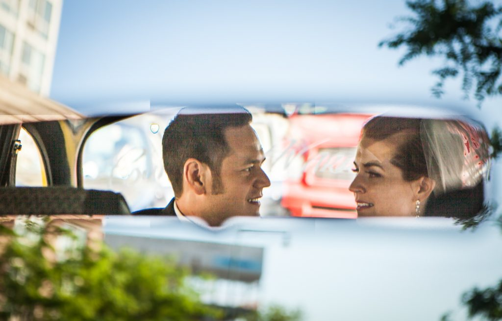 Reflection in taxicab rearview mirror of bride and groom