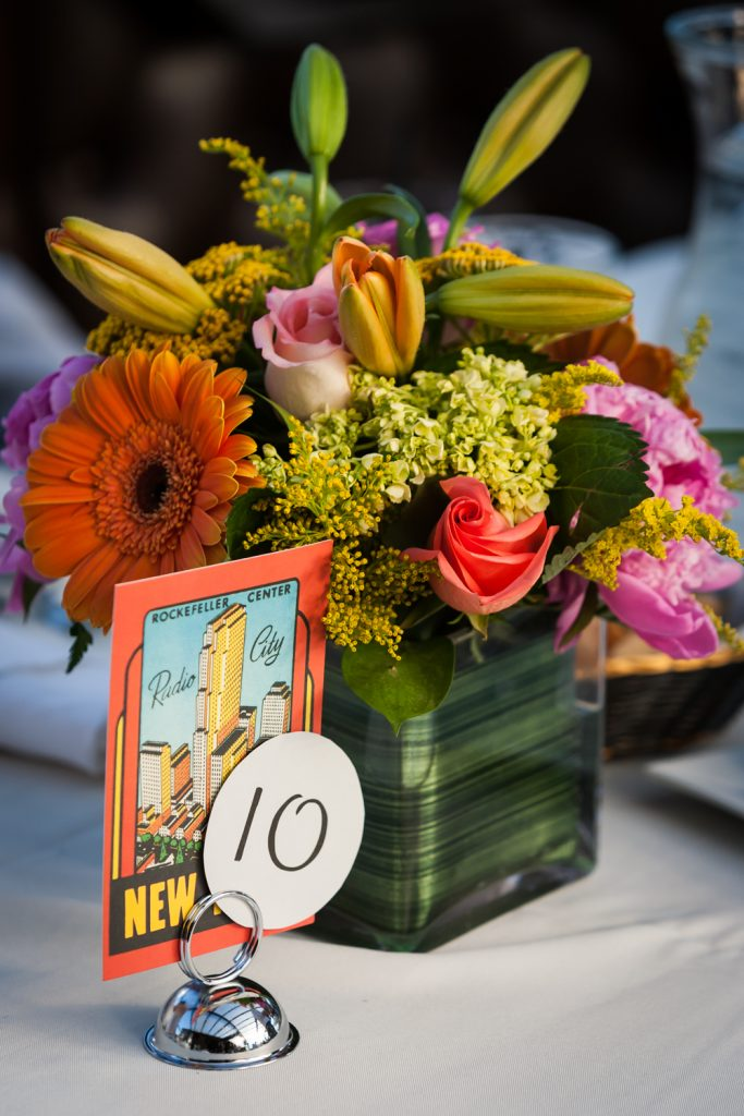 Flower centerpiece and table number with NYC postcard at a Ravel Hotel Penthouse wedding