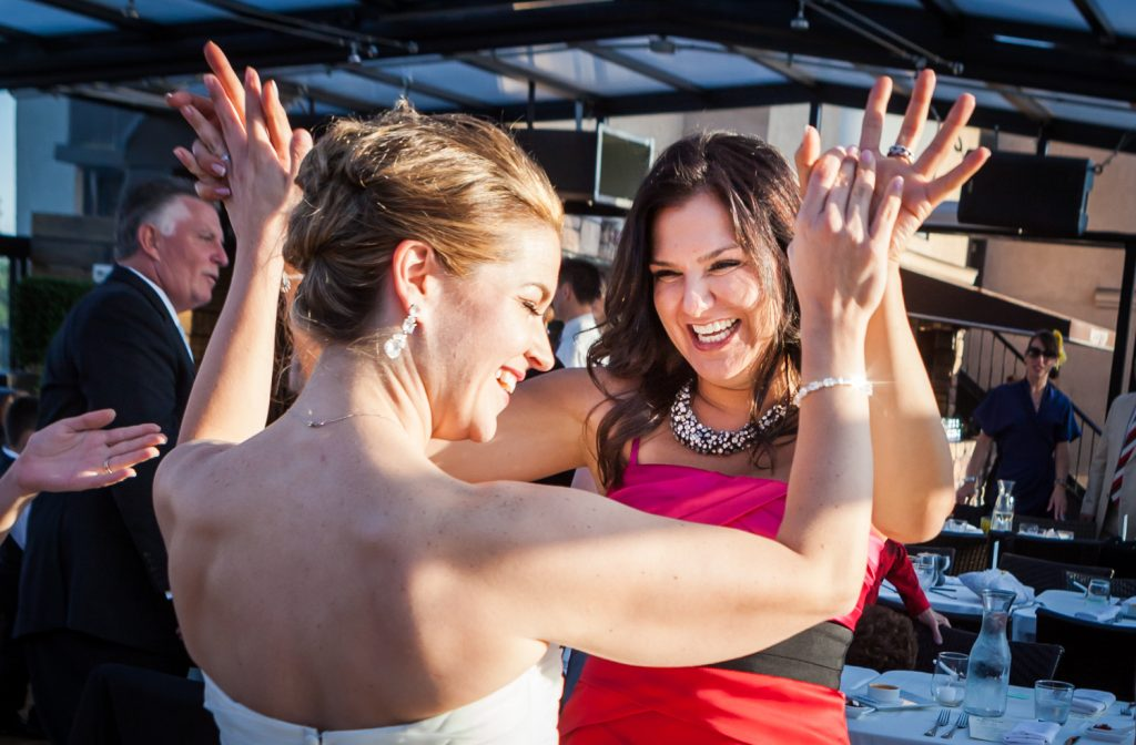 Bride and guest high-fiving at a Ravel Hotel Penthouse wedding