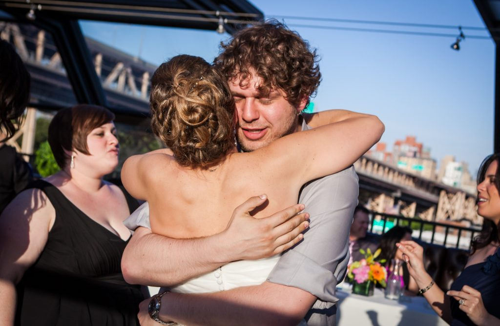 Guest hugging bride at a Ravel Hotel Penthouse wedding