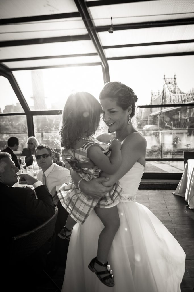 Bride holding little girl at a Ravel Hotel Penthouse wedding