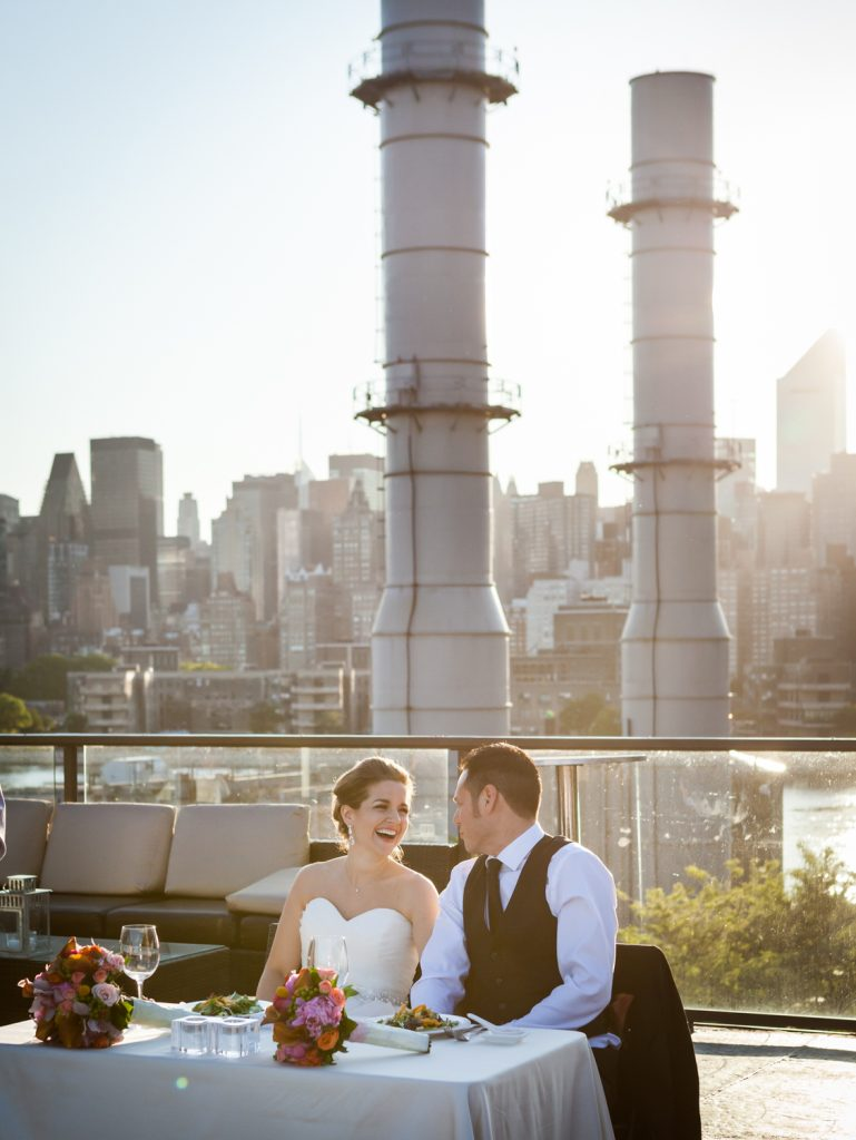 Bride and groom at sweetheart table with Long Island City smoke stacks in background at a Ravel Hotel Penthouse wedding