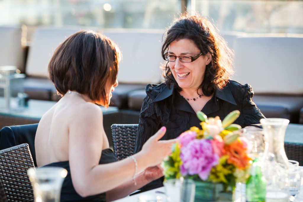 Two female guests talking at a Ravel Hotel Penthouse wedding