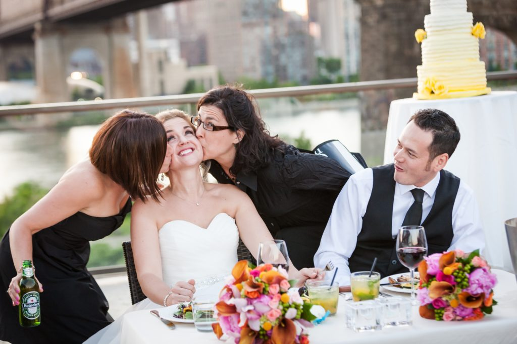 Groom watching as two guests kiss bride on both cheeks