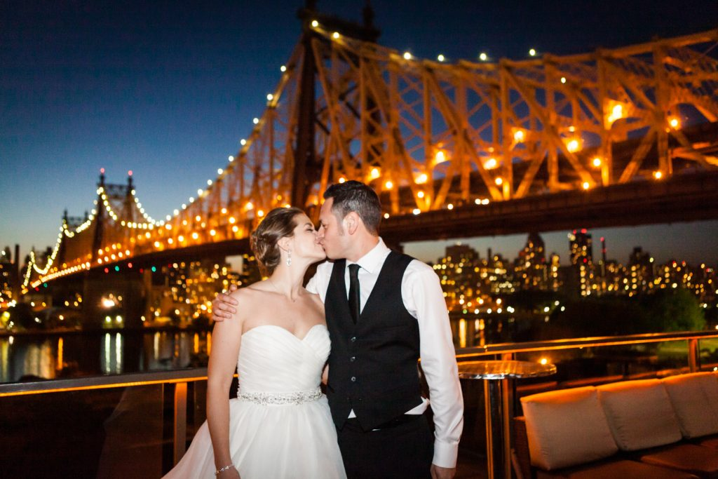Bride and groom kissing with Queensborough Bridge in the background at a Ravel Hotel Penthouse wedding
