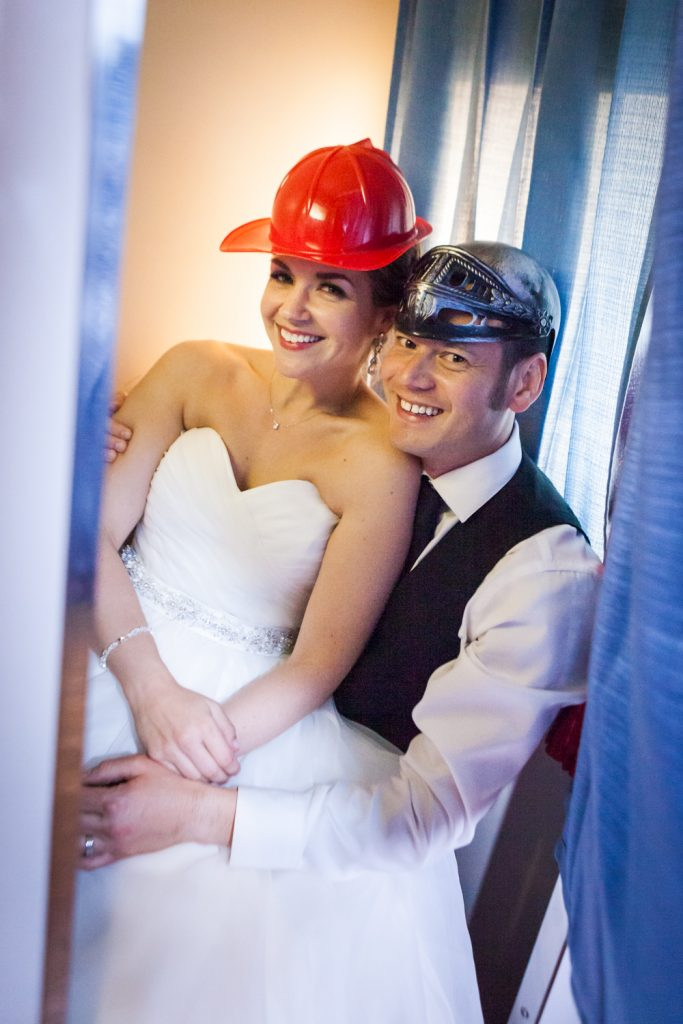 Bride and groom wearing silly hats in a photo booth at a Ravel Hotel Penthouse wedding