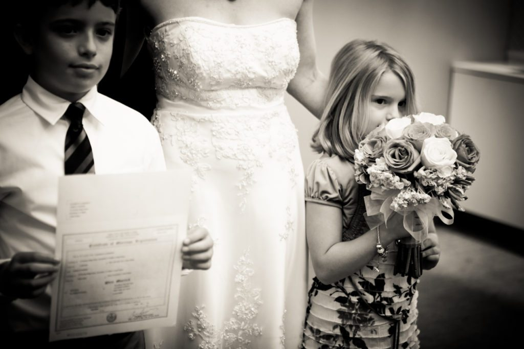 Little girl sniffing the bouquet at a NYC City Hall wedding, by Kelly Williams
