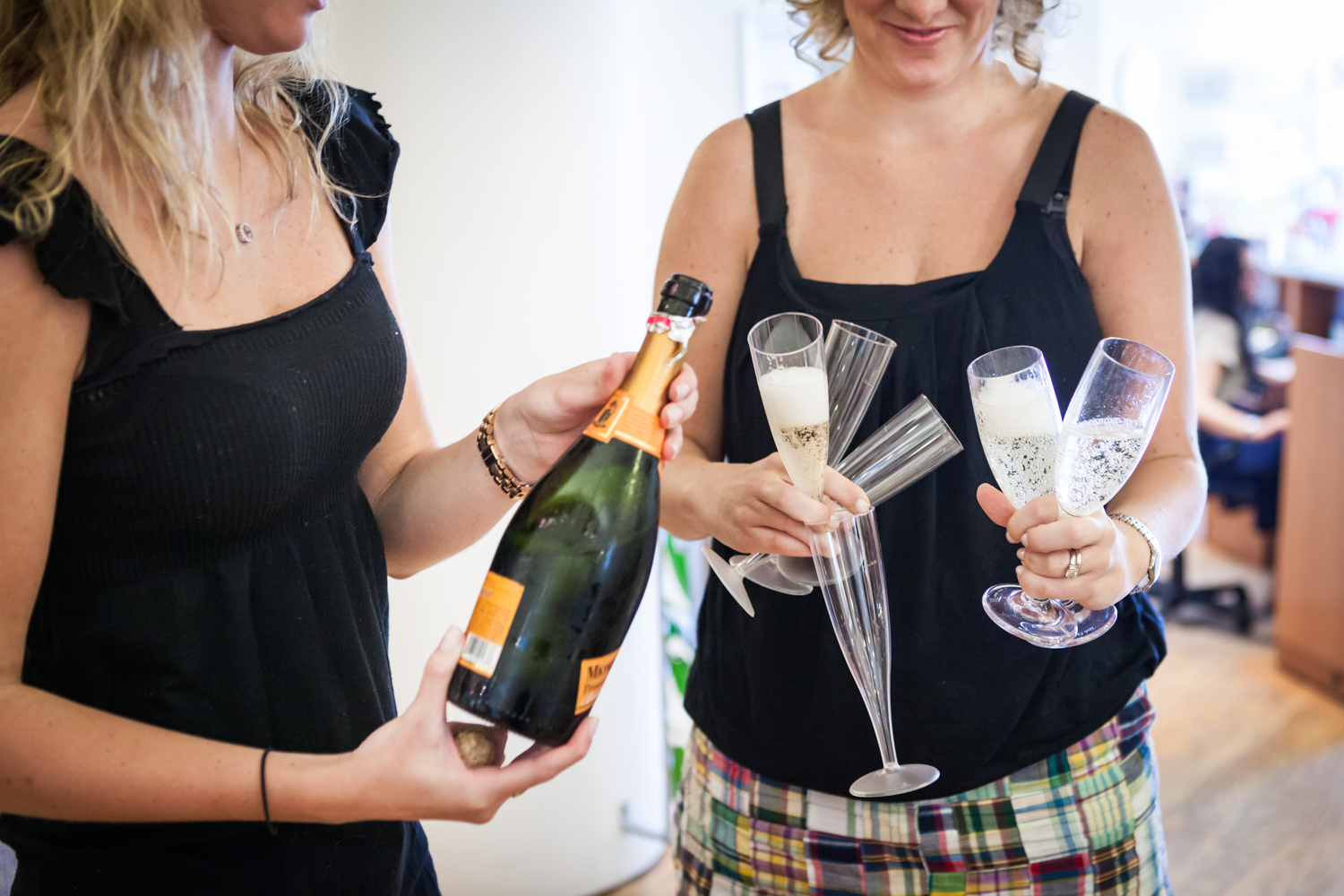 Close up on bridesmaids holding champagne bottle and many champagne glasses