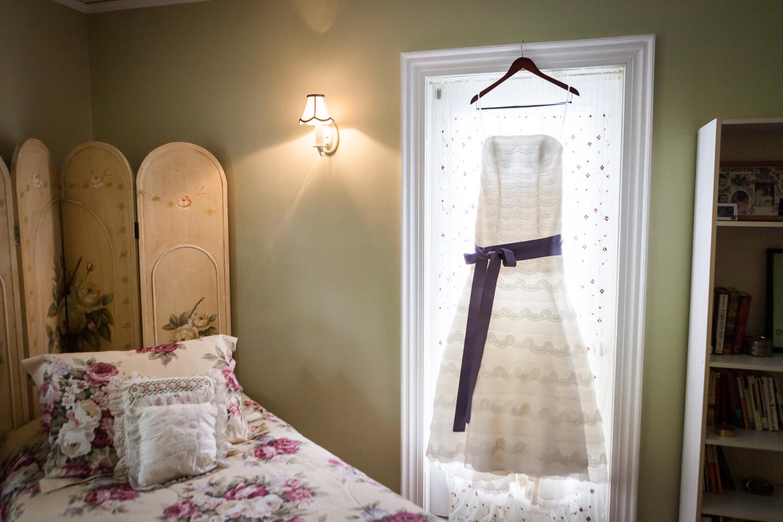 Wedding dress hanging in window of bedroom