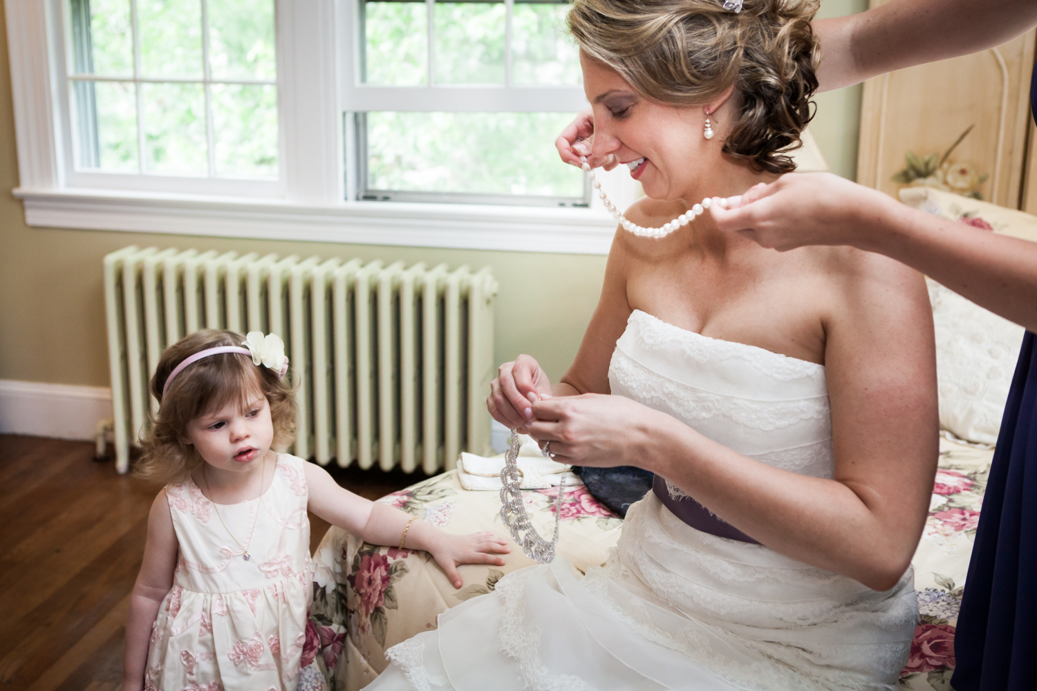 Little girl watching bride put on jewelry