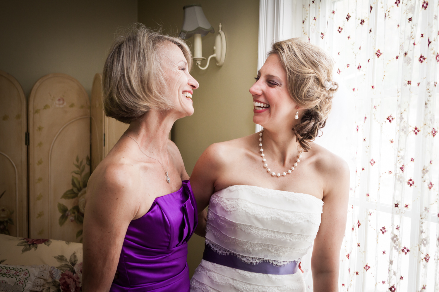Bride and mother laughing by window