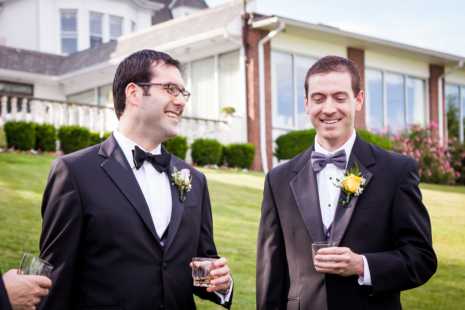 Groom and groomsmen drinking on front lawn at a Davenport Mansion wedding