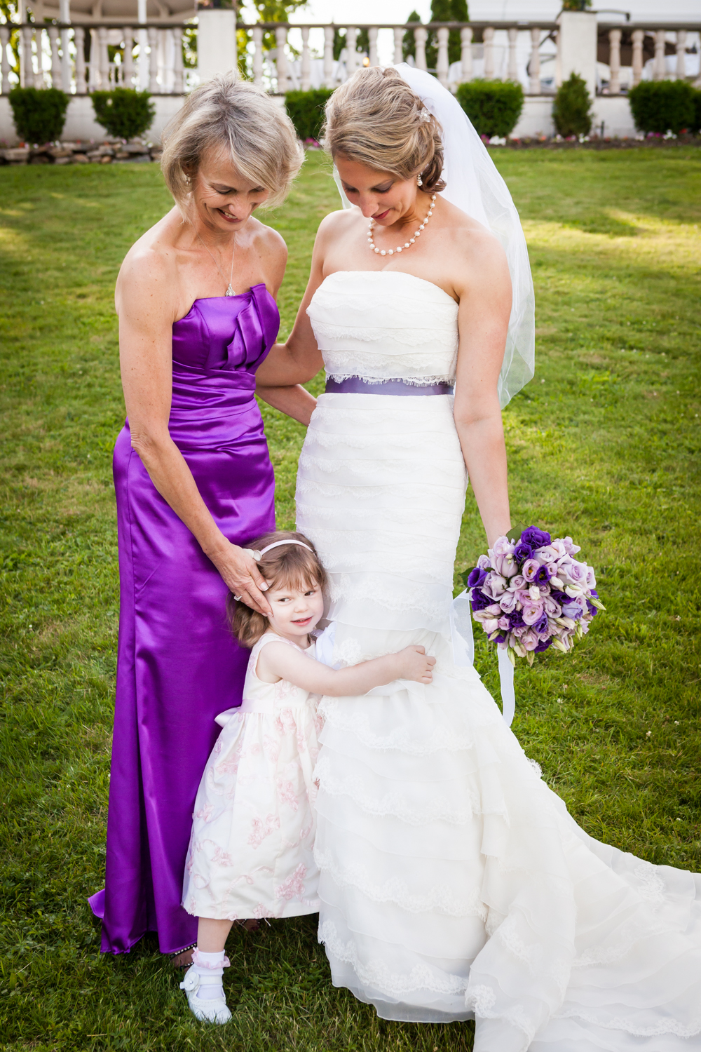 Little girl hugging bride standing by her mother at a Davenport Mansion wedding