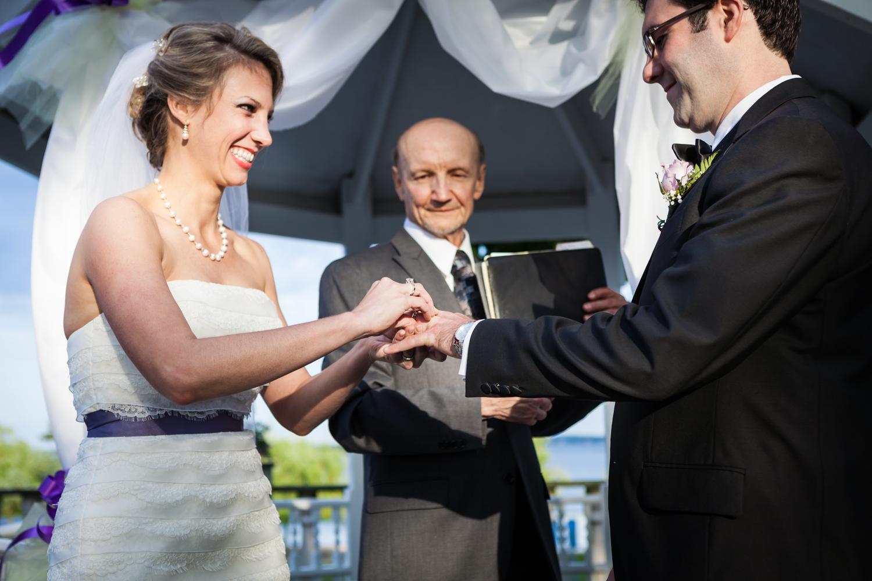 Bride putting ring on groom's finger at a Davenport Mansion wedding
