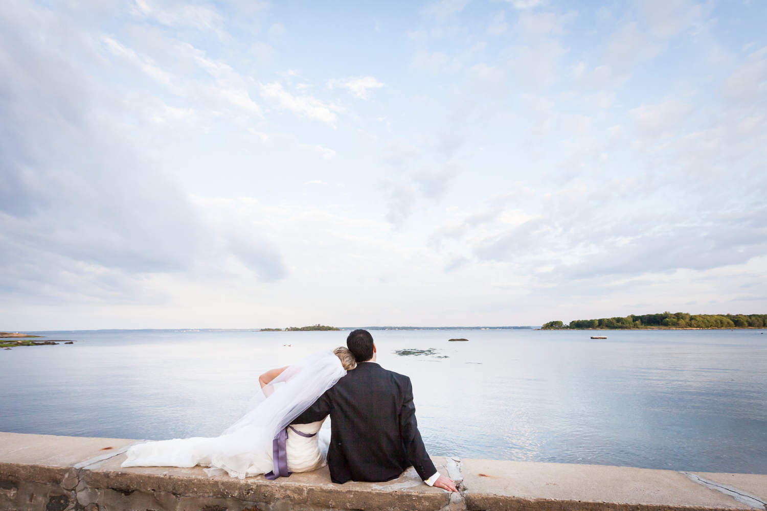 Bride and groom sitting on wall watching water at a Davenport Mansion wedding