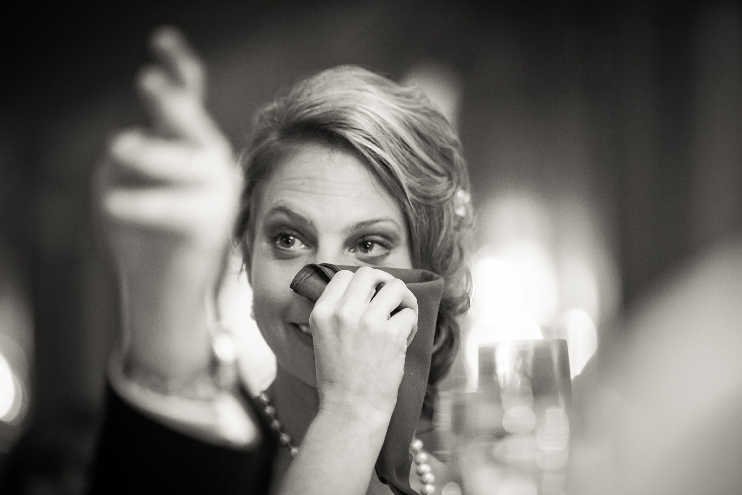 Black and white photo of bride wiping away tear
